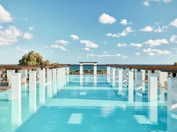 Blick über den wunderbaren türkisfarbenen Pool mit Entspannungsliegen