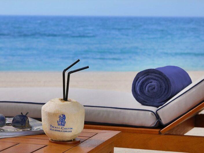 Mit einer frischen Kokosnuss am Strand
